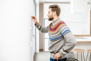 Man in sweater adjusting room temperature with electronic thermostat at home